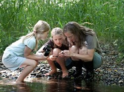 Leah's kids, Maya and Bryn, and A Rocha's intern Audrey explore the wonder of a river.