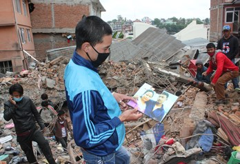 A survivor of Swayambu church collapse shows photo of fellow church member who died.