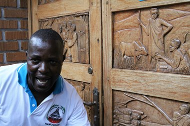 Tour guide and site historian Ben Tenywa poses in front of a door at the Catholic Martyrs' Shrine at Namugongo. The door depicts the young men, who were tortured and murdered for their faith in 1886. Pope Francis visits the shrine this week.
