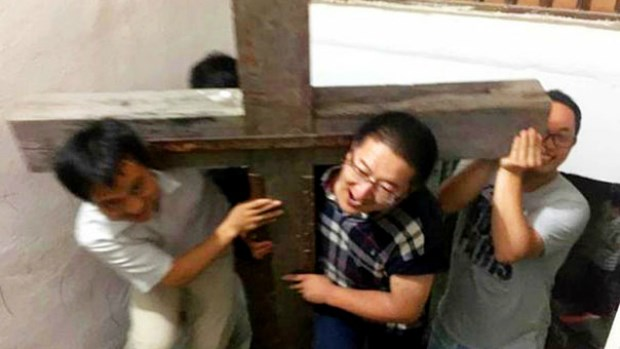 Zhang Kai (center) helps carry a wooden cross at Xialing Church, hours before his arrest.