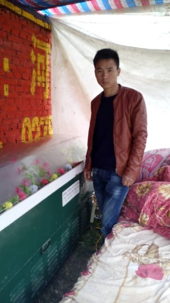 Ding's son stands next to where her body is being stored.