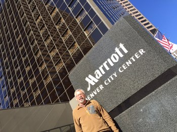Dave Collins standing in front of the Marriott hotel in Denver where he serves as a housekeeper