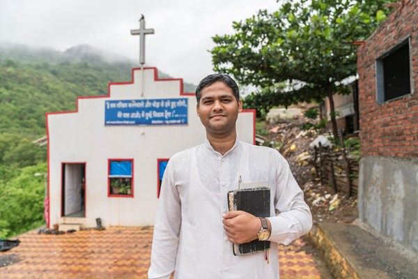 A pastor in front of the church he revived in a Mumbai slum.