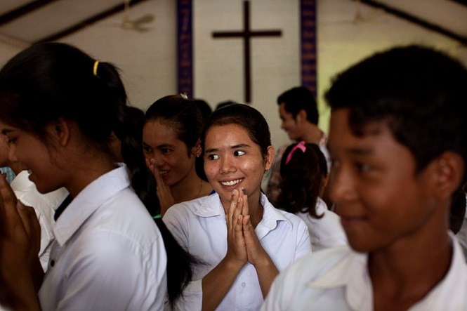Members of Grace Brethren Church in Battambang extend traditional bows to one another during the passing of the peace.