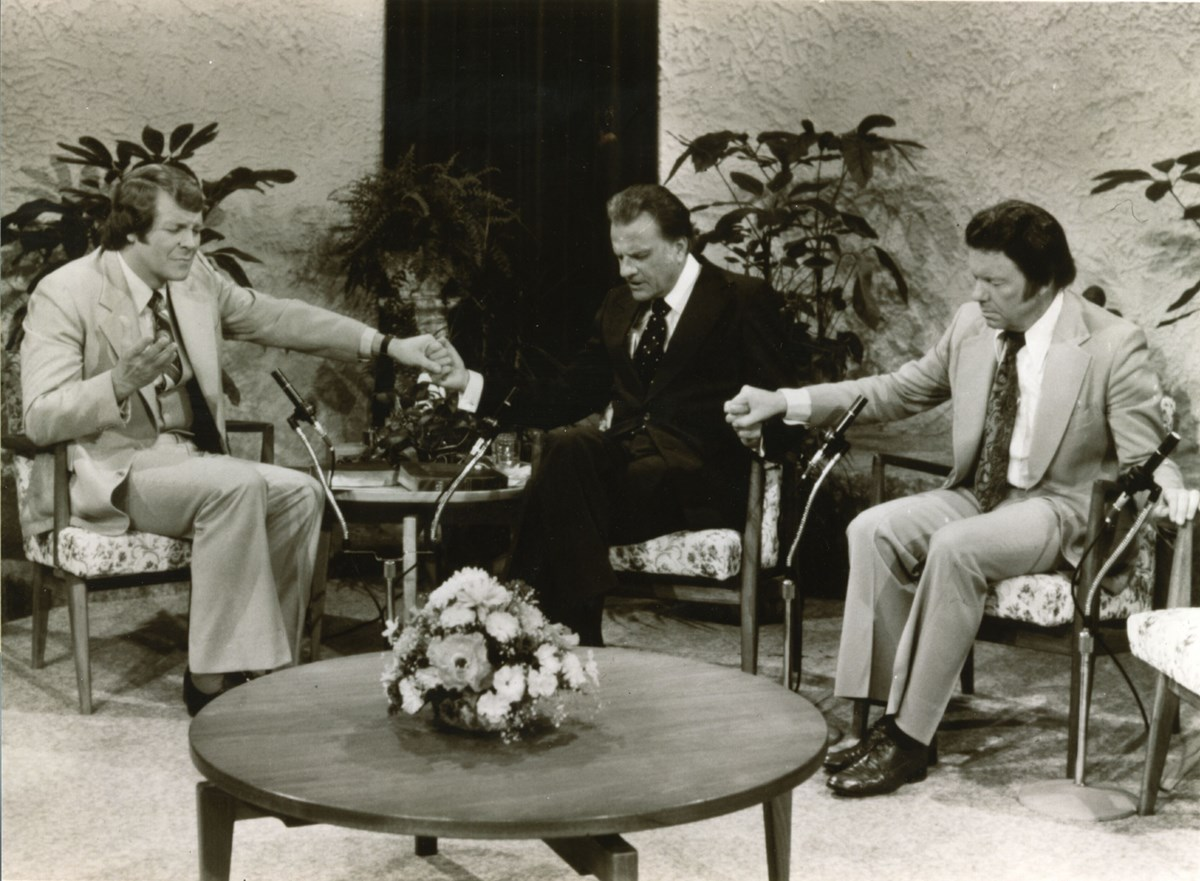 David Mainse prays with Billy Graham and evangelist John Wesley White.