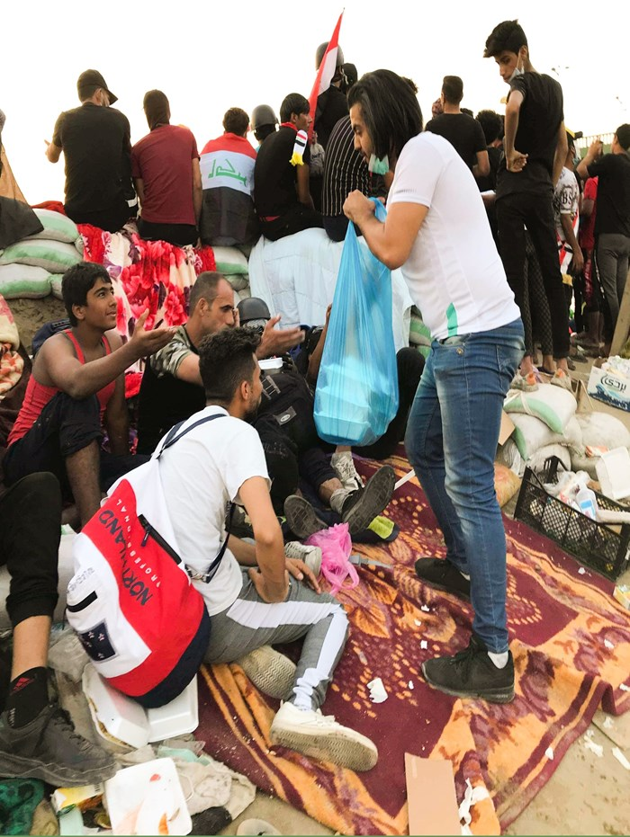 A member of National Baptist Church gives food to protesters in Baghdad.