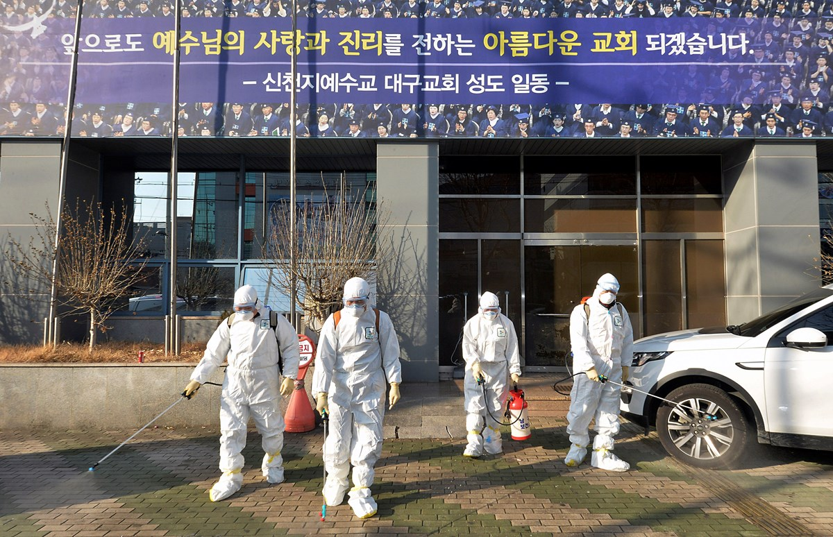 Workers wearing protective gears spray disinfectant against the coronavirus in front of a Shincheonji church in Daegu, South Korea.