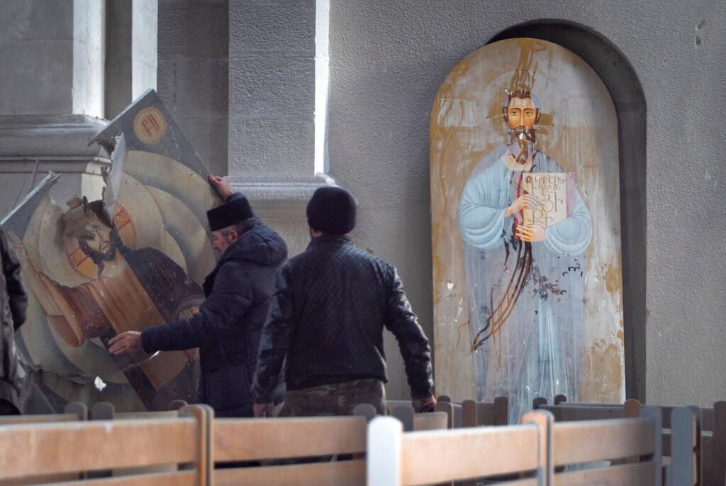 Men lift an icon in the Holy Savior Cathedral damaged by shelling during a military conflict, in Shushi, outside Stepanakert, self-proclaimed Republic of Nagorno-Karabakh on October 8.