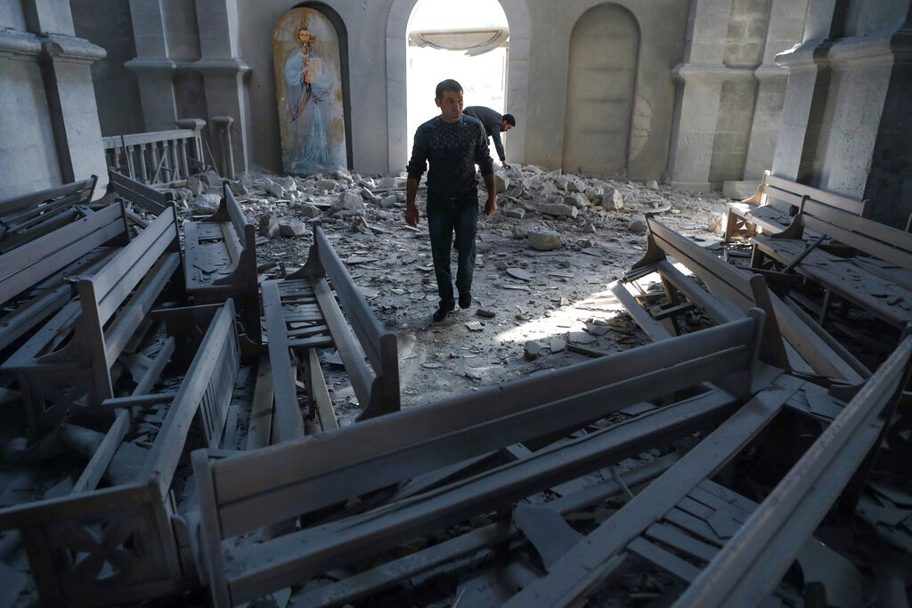 A man walks in rubbles of the Ghazanchetsots (Holy Saviour) Cathedral in the city of Shusha, some 15 kilometers from the Nagorno-Karabakh province's capital Stepanakert on October 8.