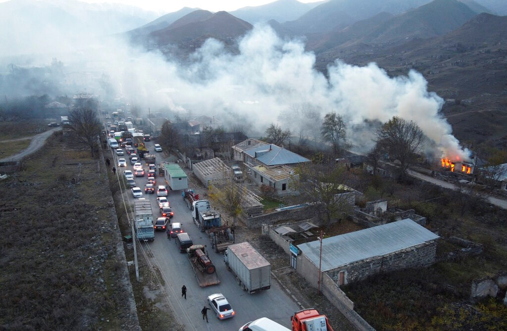 Smoke rises from a burning house as cars and trucks stuck in a huge traffic jam climbing along the road from Kelbajar leaving the separatist region of Nagorno-Karabakh to Armenia on Nov. 14.