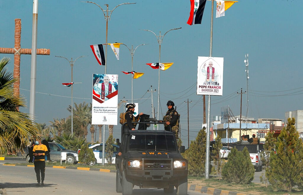 Iraqi security forces in Qaraqosh pass by the flags of Iraq and the Vatican and posters announcing the upcoming visit of Pope Francis on February 22.
