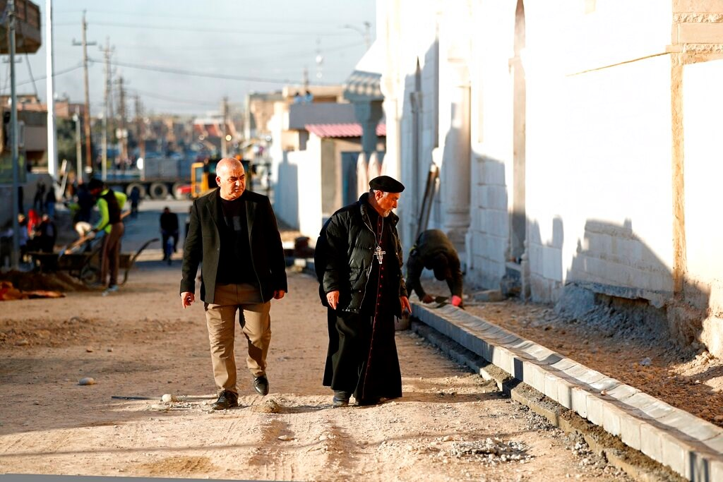 A priest watches workers fix a street destroyed during clashes against Islamic State militants in Qaraqosh, Iraq, on February 23.