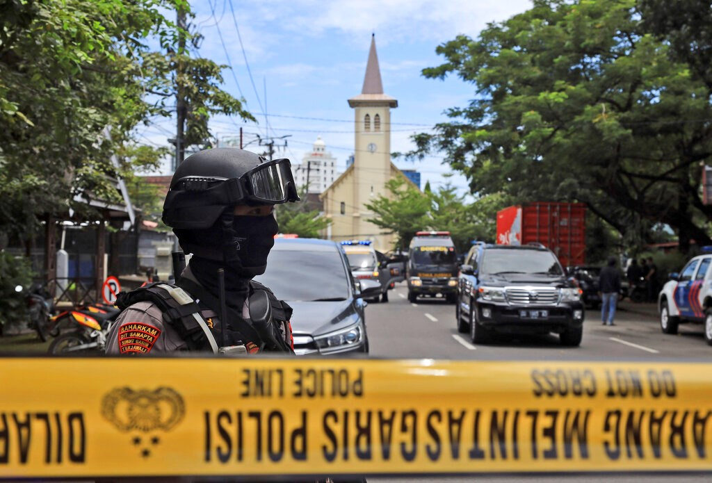 An Indonesian police officer stands guard near the Sacred Heart of Jesus Cathedral in Makassar, South Sulawesi, where an explosion went off on Palm Sunday.