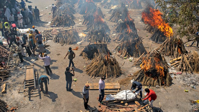 Image: Altaf Qadri / AP Photo - Multiple funeral pyres of Indian victims of COVID-19 burn in a New Delhi area converted for mass cremation on April 24.