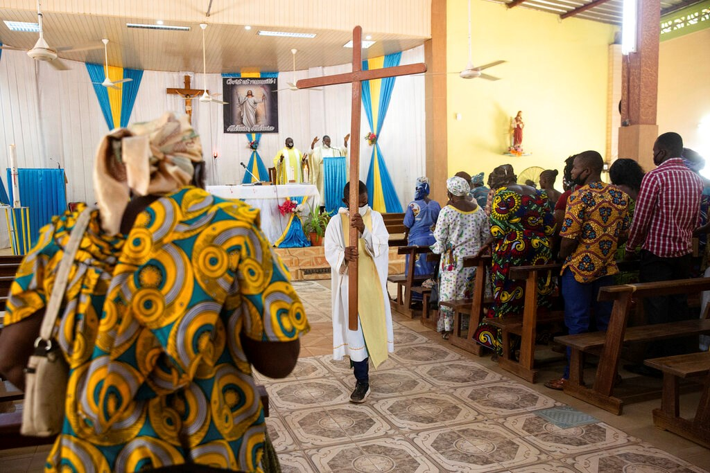 An altar boy carries a cross as Noel Henri Zongo, priest at the Church of the Sangoulé Lamizana military camp in Ouagadougou, Burkina Faso, celebrates Mass on April 11. Just seven chaplains are charged with spiritually advising some 11,000 soldiers and helping maintain their morale.