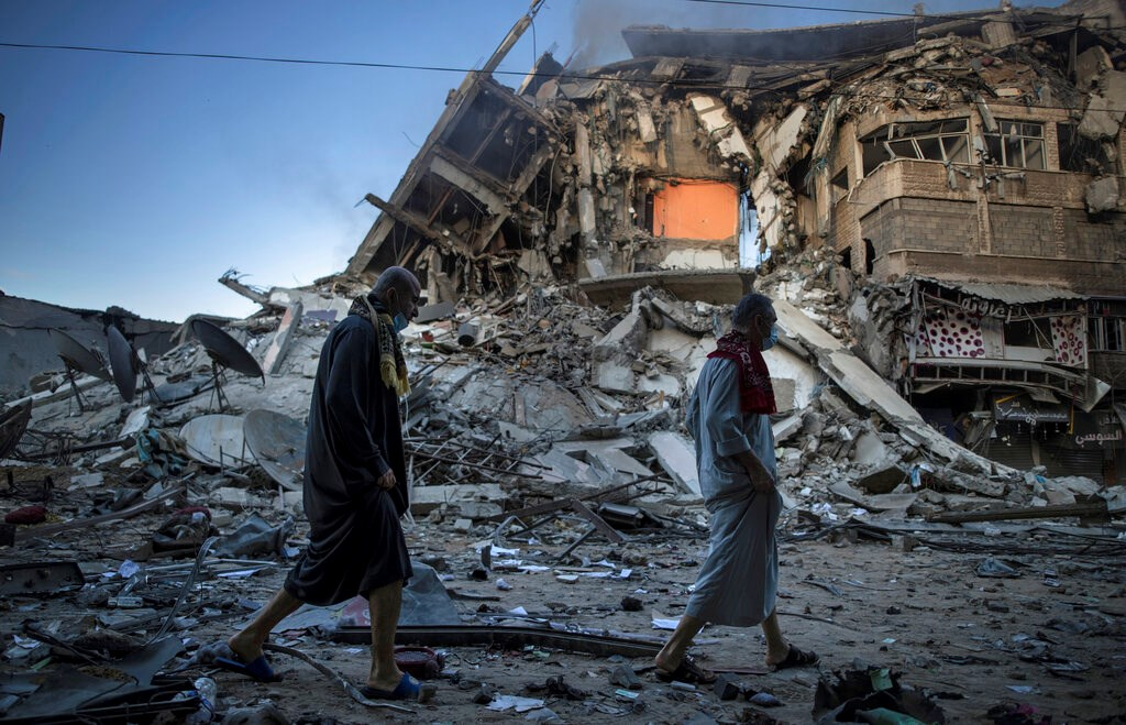Palestinians walk next to the remains of a destroyed 15-story building hit by Israeli airstrikes on Gaza City on May 13, 2021.