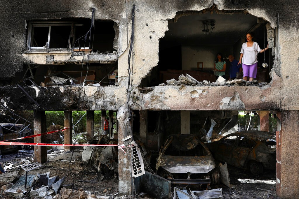Members of the Sror family inspect the damage to their apartment in Petah Tikva in central Israel after it was hit by a rocket fired from the Gaza Strip on May 13, 2021.