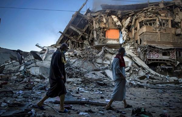 I palestinesi camminano accanto ai resti di a distrutto edificio di 15 piani colpito da israeliani attacchi aerei su Gaza City il 13 maggio 2021.