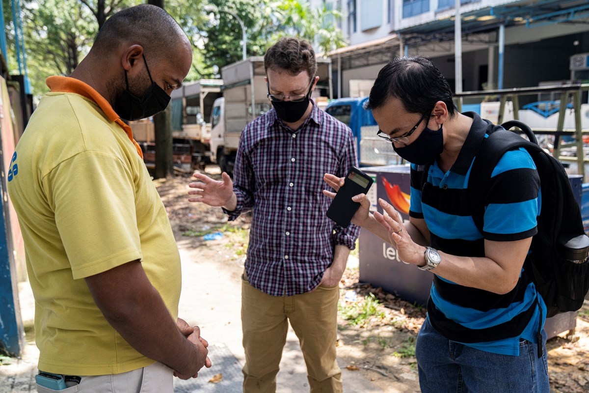 Pastor Guoliang Wong (right) and Thomas Franks (middle) pray together with Francis Xavier (left), a Christian migrant worker outside a factory-converted dormitory in Singapore in April 2020.