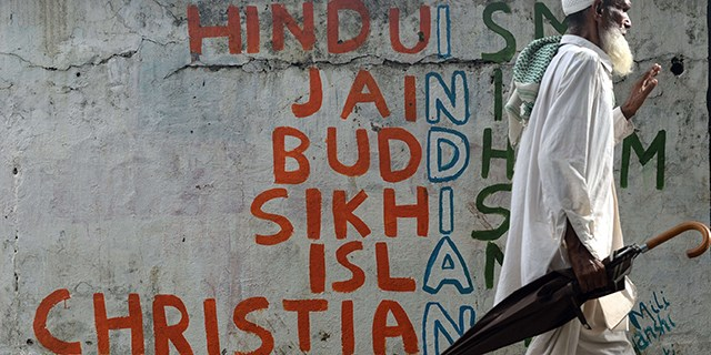 An Indian man walks past a wall graffiti on various religions in Mumbai on June 25, 2015.