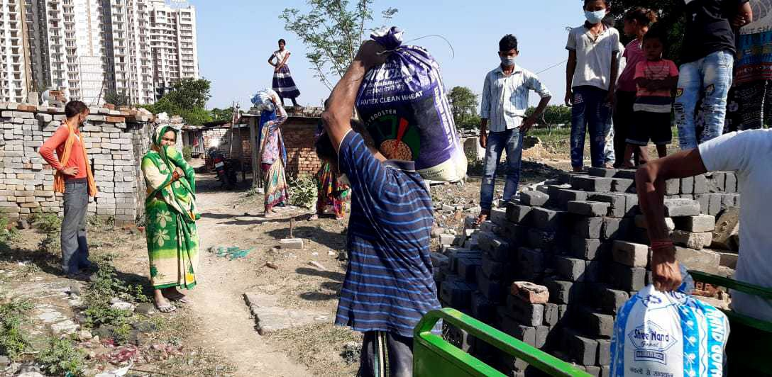 Volunteers distribute groceries to daily-wage workers in Delhi.