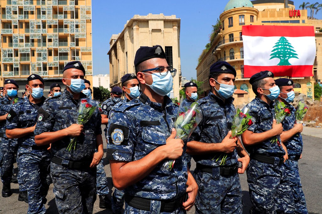 Police hold flowers to mark the first anniversary of Beirut's massive 2020 seaport blast on Wednesday, August 4, 2021.