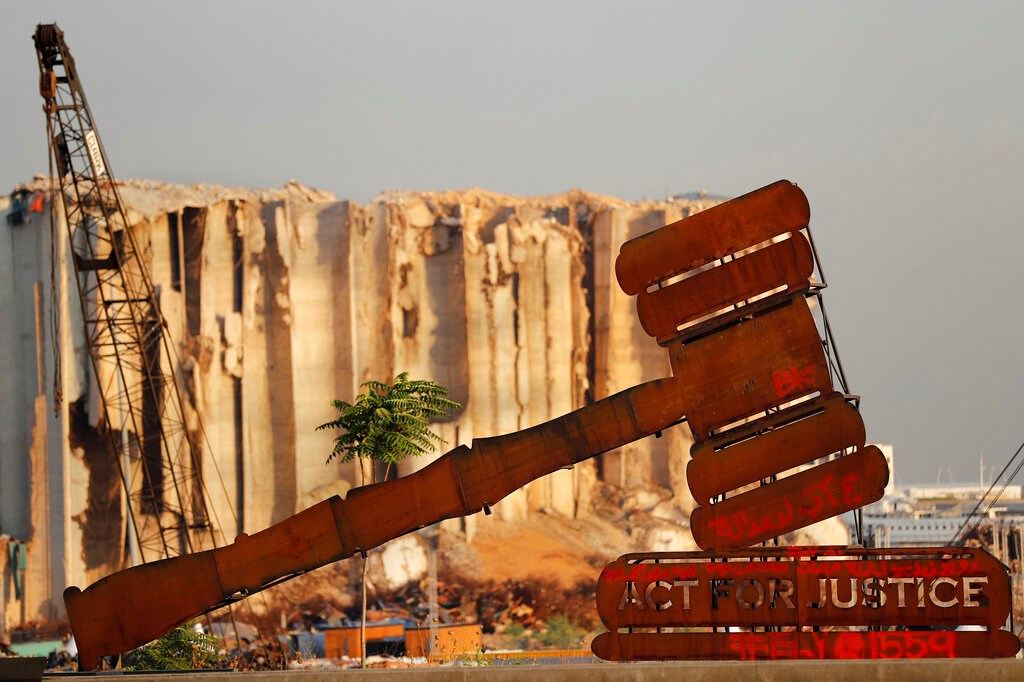 A justice symbol monument is seen in front of towering grain silos that were gutted in the massive August 2020 explosion at the port that claimed the lives of more than 200 people, in Beirut, Lebanon on August 4, 2021.