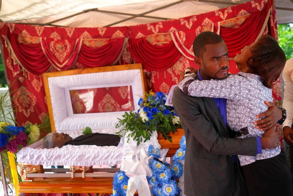 The son and mother of Baptist church minister Andre Tessono, who was killed during the 7.2 magnitude earthquake that hit the area eight days ago, mourn during his funeral in the Picot neighborhood in Les Cayes, Haiti, Sunday, Aug. 22, 2021.