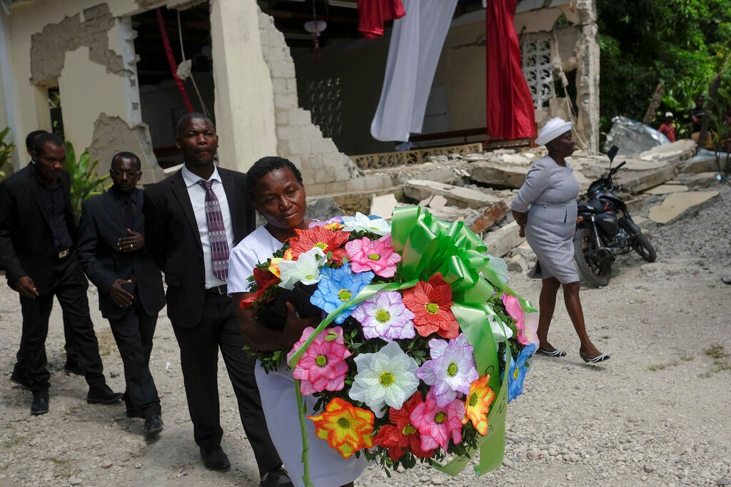 People carry a flower offering next to the earthquake-destroyed church where Baptist church minister Andre Tessono died, during his funeral in the Picot neighborhood in Les Cayes, Haiti, Sunday, Aug. 22, 2021, eight days after a 7.2 magnitude earthquake hit the area.