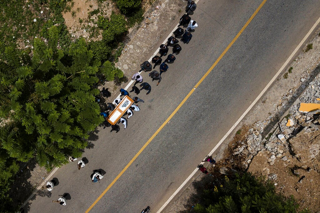 The coffin with the body of Baptist church minister Andre Tessono, who was killed during the 7.2 magnitude earthquake that hit the area 8 days ago, is carried to the cemetery during his funeral in the Picot neighborhood in Les Cayes, Haiti, Sunday, Aug. 22, 2021.