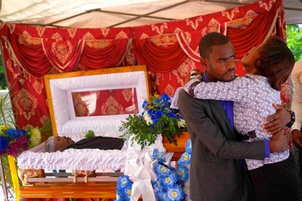 Le fils et la mère du ministre de l'Église baptiste Andre Tessono pleurent lors de ses funérailles dans le quartier Picot aux Cayes, Haïti, dimanche 22 août 2021.