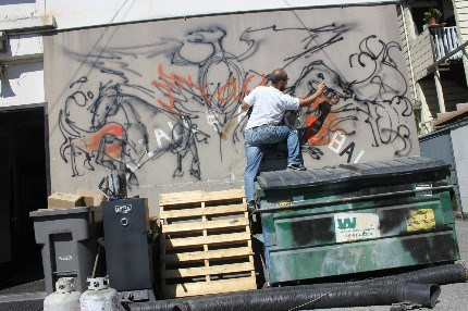 Kim painting dinosaurs on a back wall of the Oakland Fire Department (with permission).