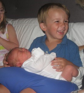William holds his new baby cousin