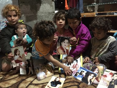 Refugee children from Sinjar display photos of their sister killed by ISIS.