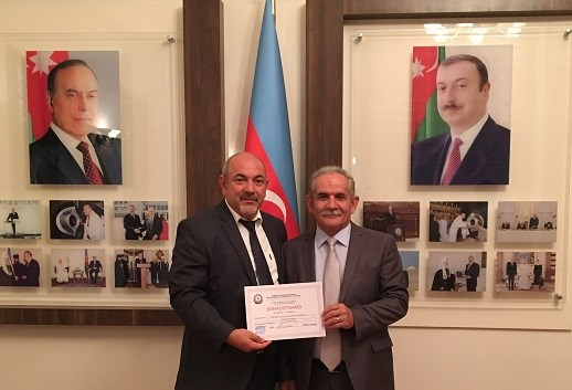 Rasim Khalilov (left), chairman of the Bible Committee, holds the new certificate of registration.