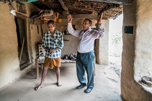 Pastor Bhagwana Lal prays with a tribal neighbor.