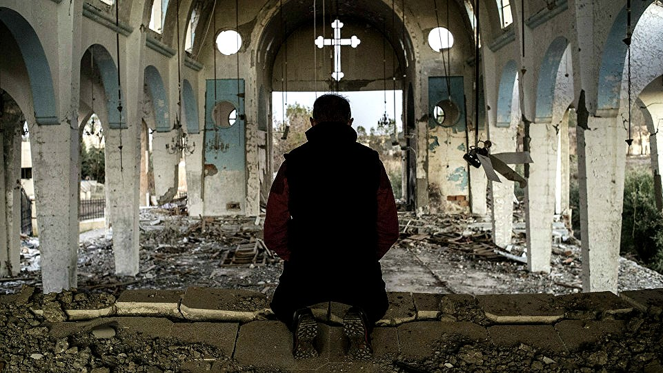 A local Christian prays in the ruins of a church destroyed by ISIS in Syria's Hasakah province.