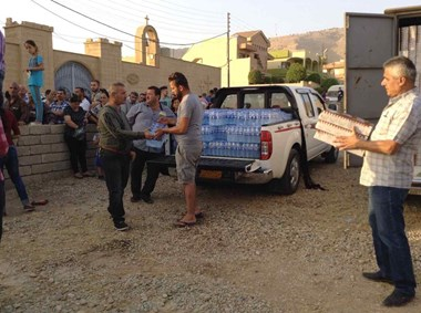 Displaced Iraqi Christians receive aid at St. Qardakh church in al-Qosh.