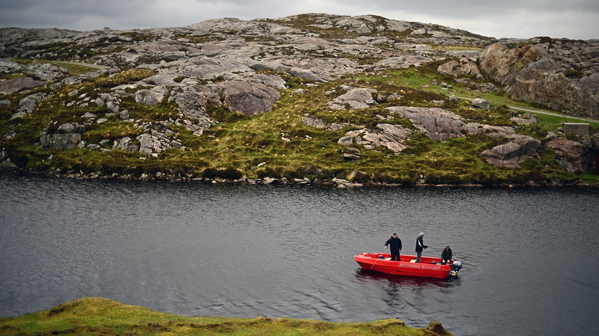 Men fly fish in a boat on a loch in Harris.