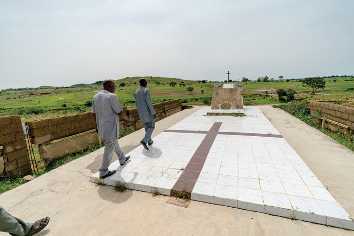 Bulus Ezekiel, a local evangelist, escorts a visiting pastor to the mass grave in Dogonawa (now called Dembrook) where Fulani militants massacred almost 500 Christians in 2010. He says an annual memorial service was canceled after too many villagers fell ill from grief.