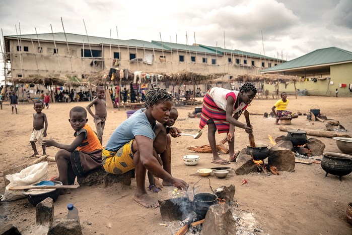 At one of Benue's newest camps for displaced farmers, mothers cook a meager lunch while children gather under thatch trellises in an attempt to maintain their schooling. The Makurdi camp is so crowded, the men sleep outside unless it rains.