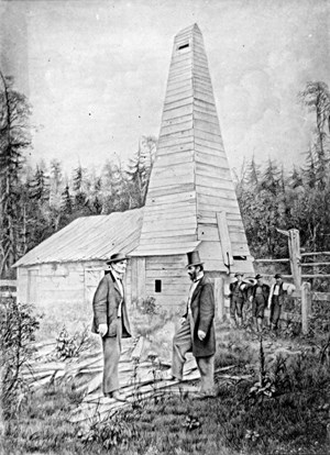 Drake (right) in front of his first oil well