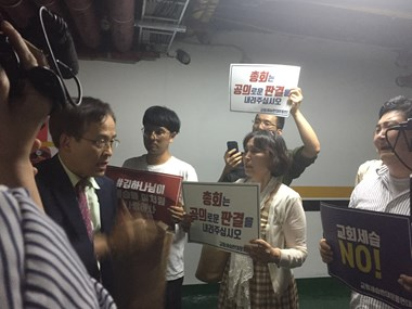 Students and activists question a court member in the parking lot.